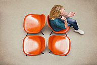 Woman sitting on chairs talking on the phone - MAEF011428