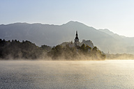 Slovenia, Gorenjska, Bled, Bled Island, Assumption of Mary's Pilgrimage Church and Lake Bled in morning fog - RUEF001673