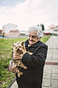Happy senior woman with Yorkshire Terrier on her arms - RAEF000973