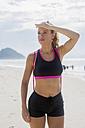 Brazil, Rio de Janeiro, sportive woman standing on the beach shielding her eyes - MAUF000375
