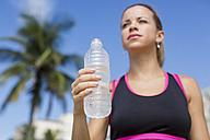 Brazil, sportive woman holding water bottle - MAUF000381