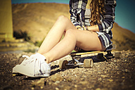 Teenage girl sitting on longboard, partial view - SIPF000294