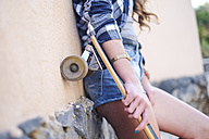 Portrait of smiling teenage girl with longboard leaning against wall, partial view - SIPF000297