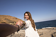 Spain, happy teenage girl holding hand of her friend - SIPF000306