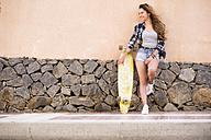 Portrait of smiling teenage girl with longboard leaning against wall - SIPF000309
