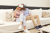 Couple sitting head to head on couch at home using Virtual Reality Glasses - MAEF011432