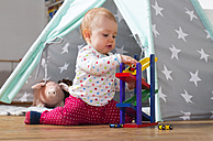 Baby girl playing with wooden toys on the floor at home - WWF003938