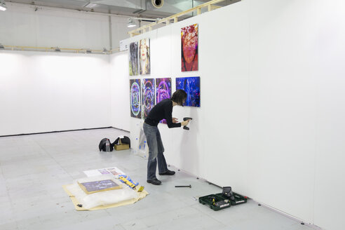 Artist preparing exhibition at art fair - NDF000578
