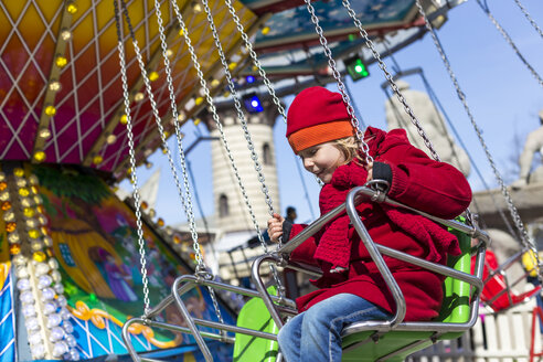 Happy little girl on chairoplane at fun fair - JFEF000773