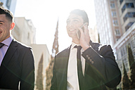 Businessman on cell phone in backlight with colleague - LEF000024
