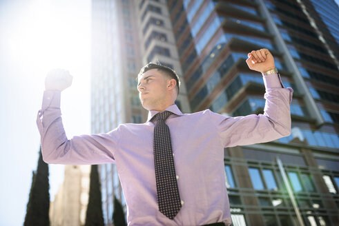 Confident businessman outdoors raising his arms - LEF000033