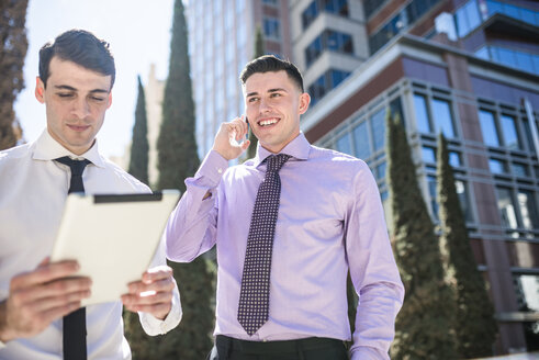 Two businessmen outdoors with tablet and cell phone - LEF000036