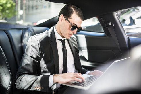 Businessman in car using laptop - LEF000042
