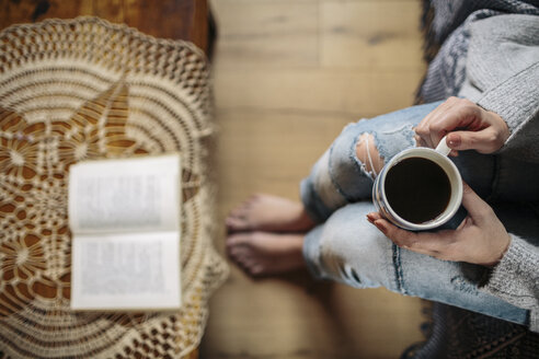 Young woman at home relaxing with cup of coffee and a book - HAPF000306