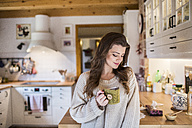 Young woman at home drinking cup of coffee in kitchen - HAPF000312