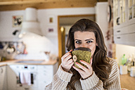 Young woman at home drinking cup of coffee in kitchen - HAPF000315