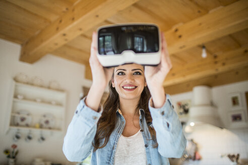 Young woman at home using Virtual Reality goggles - HAPF000330