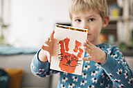 Little boy presenting self-made Easter card - MFF002956