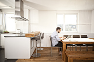 Man sitting at table in his open plan kitchen using laptop - MFRF000527