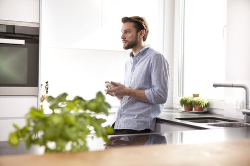 Pensive young man with cup of coffee standing in his kitchen - MFRF000539