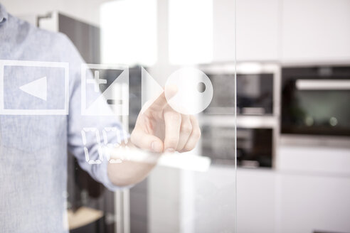 Man's hand using touchscreen of oven in his kitchen - MFRF000545