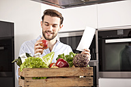 Portrait of young man with wooden box of fresh vegetables and shopping list in his kitchen - MFRF000548