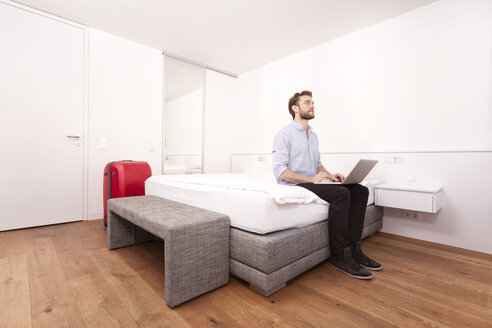 Man sitting with laptop on a hotel bed - MFRF000554