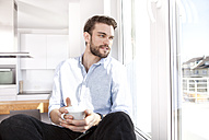 Young man with coffee cup sitting on window sill looking through window - MFRF000572