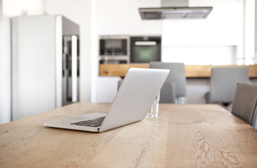 Laptop on wooden table in an open plan kitchen - MFRF000590