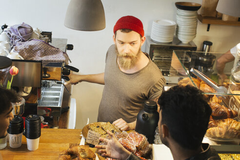Man talking to barista at cafe counter - JUBF000133