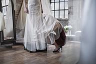 Wedding dress designer crouching under wedding dress - ZEF008649