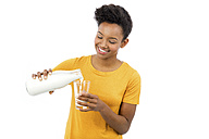 Portrait of smiling young woman pouring milk in a glass in front of white background - GDF000980