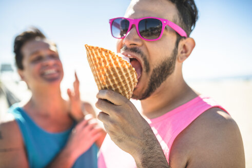 Portrait of man with pink sunglasses eating icecream - LEF000051