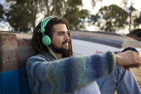 Young man with dreadlocks listening to music with headphones - KIJF000295
