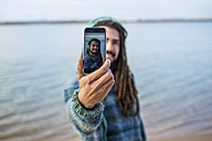 Young man with dreadlocks he take selfie with a smartphone on the beach - KIJF000298