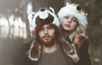 Portrait of young couple wearing animal hats in the woods - RTBF000070