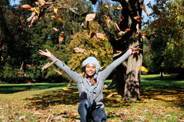 Happy young woman throwing autumn leaves in the air - KLR000294