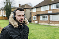 Portrait of man listening music with headphones outdoors - MGOF001682