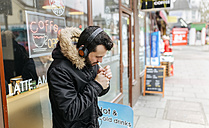UK, London, man with headphones standing in front of window display lighting a cigarette - MGOF001685