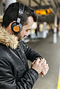 Man with headphones standing on platform using smartwatch - MGOF001688