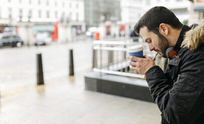 UK, London, man with coffee to go lighting a cigarette - MGOF001691