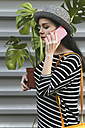 Woman telephoning with smartphone carrying a Monstera deliciosa - RTBF000076