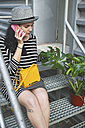 Young woman sitting on stairs telephoning with smartphone - RTBF000079