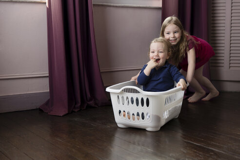Little girl pushing her little brother sitting in a laundry basket - LITF000221