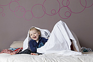 Portrait of laughing little boy sitting on parents' bed beside his sister hiding under a sheet - LITF000227