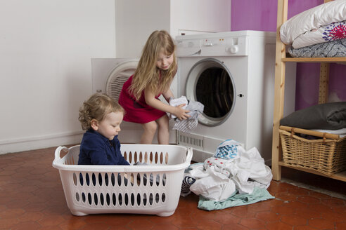 Toddler boy sitting in laundry basket while his sister emptying the tumble dryer - LITF000245