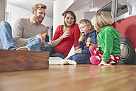 Happy family with popsicles and model car in living room - RHF001412