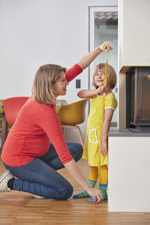 Pregnant mother measuring daughter's size - RHF001430