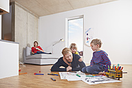Father lying on floor with children painting - RHF001448