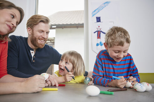 Happy family painting Easter eggs together - RHF001454
